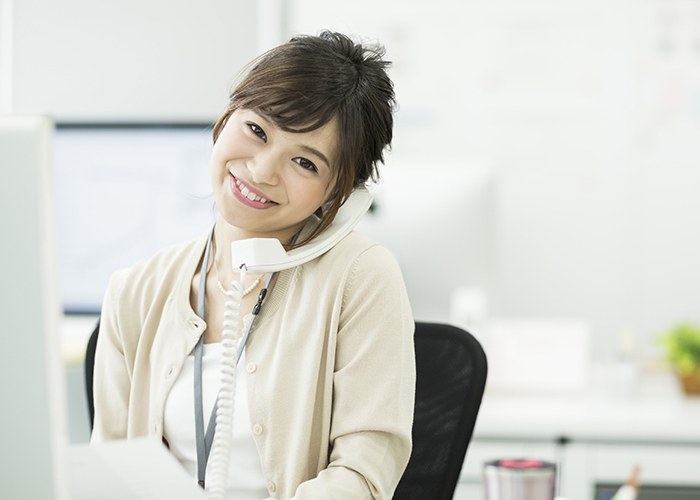 肩で受話器をおさえる笑顔の女性