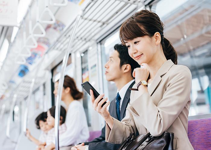 電車の中でスマホを確認する女性